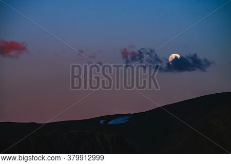Atmospheric Moon Landscape Of Twilight In Mountains. Dark Lilac Sky And Big Moon With Cloud Above Si