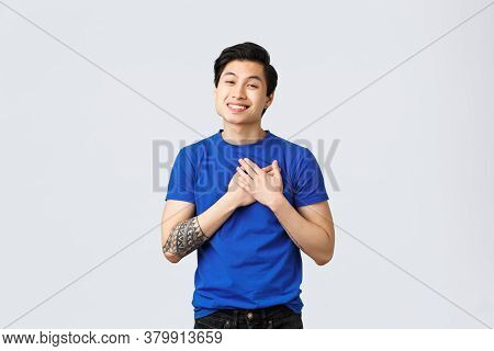 Touched And Grateful Handsome Male Asian In Blue T-shirt With Tattoos, Touching Heart And Smiling, A