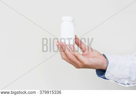 Physician Medicine Doctor Or Pharmacist Sitting At Worktable, Holding Or Showing Bottle Of Pills In