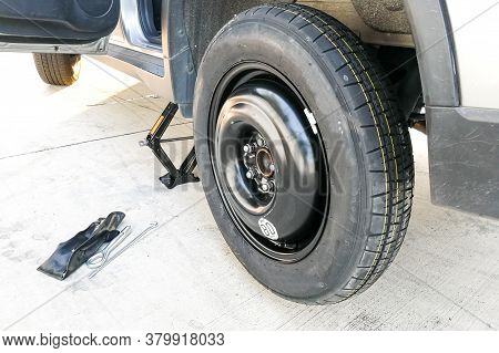 Temporary Emergency Tire Replaced Onto Car Wheel After Flat Tire