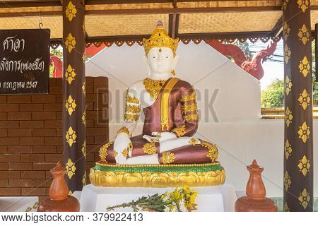 Phayao, Thailand - Dec 31, 2019: White God Statue Wear Gold Crown Sitting On Stone Base With Natural