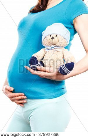 Pregnant Woman Holding Fluffy Teddy Bear For Kids At Her Belly, Concept Of Expecting For Baby And Ex