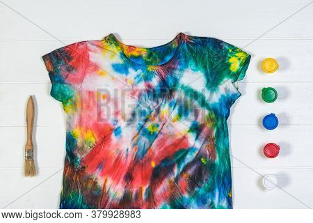 Tie Dye T-shirt With Brush And Paint On A White Table. White Clothes Painted By Hand. Flat Lay.