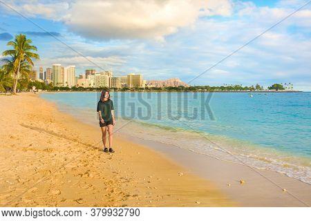 Biracial Asian Teenage Girl Walking Alone At Empty Ala Moana Beach Along The Ocean At Sunset. Waikik