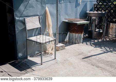 White Wooden Chair Is Placed Under Sunny Light In The Afternoon Behind Kitchen In Hong Kong China As
