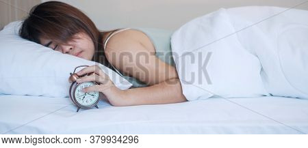Alarm Clock And Asian Woman Hand Stop Time In Bed While Sleeping, Young Adult Female Wake Up Late In