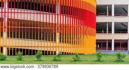 Commercial City Building Construction With Red Orange Scaffolds And Green Bushes On Grass Of Flowerb