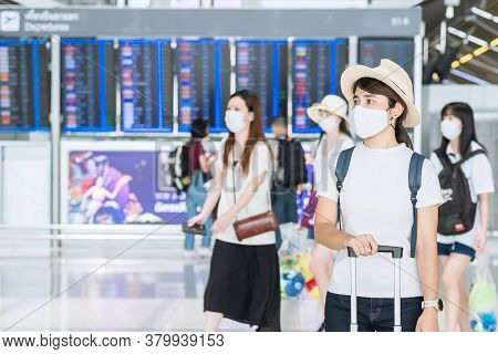 Young Female Wearing Face Mask With Luggage Checking Flight Time In Airport, Protection Coronavirus