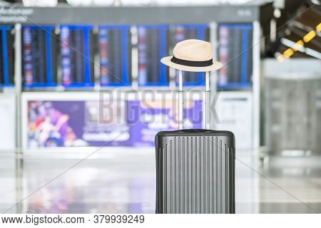 Luggage Bag With Hat In International Airport Terminal, Trolley Suitcase With Information Board In A
