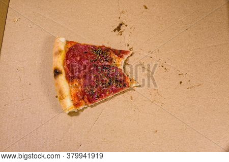 Last Piece Of Pizza With Salami Sausage And Parmesan Cheese In Cardboard Box