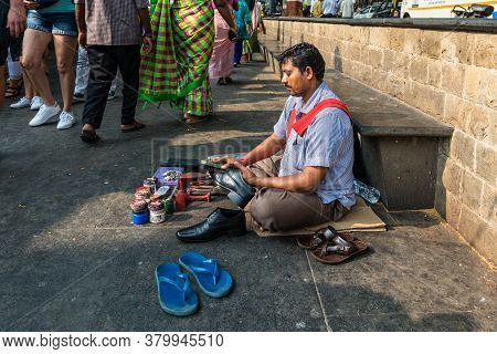 Mumbai, India - November 22, 2019: Poor Shoe Shiner Siting On The Floor And Cleans Shoes Near Gatewa