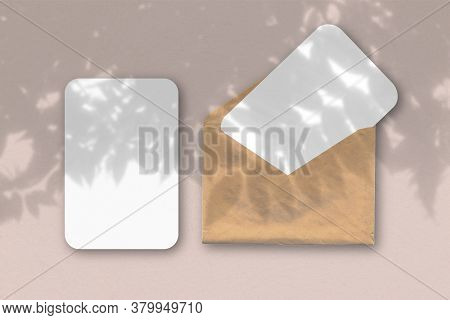 An Envelope With Two Sheets Of Textured White Paper On A Blue Table Background. Mockup With An Overl