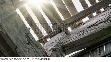 Sunlight Rays Flow Through Abandoned Shed Building Roof Holes Between Wooden Boards Against Sky Clos