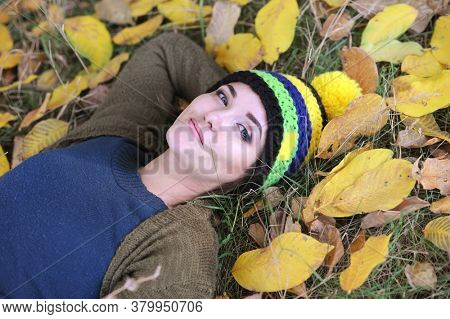 Young woman lying on a grass outdoor in autumn park, dressed in knitted hat with pompom, looking at camera