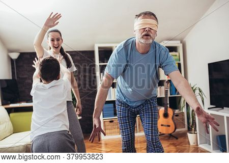 Happy Family Playing Funny Hide And Seek Game At Home, Blindfolded Father Trying To Catch Children.