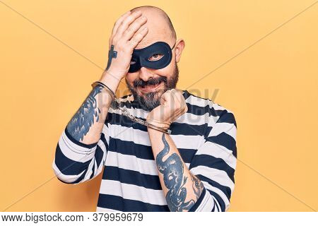 Young handsome man wearing burglar mask and handcuffs stressed and frustrated with hand on head, surprised and angry face