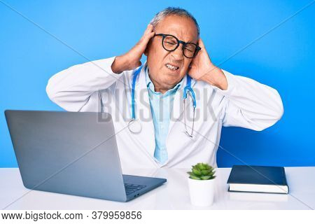 Senior handsome man with gray hair wearing doctor uniform working using computer laptop covering ears with fingers with annoyed expression for the noise of loud music. deaf concept.
