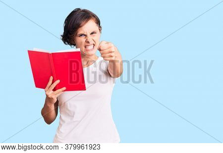 Beautiful young woman with short hair reading a book annoyed and frustrated shouting with anger, yelling crazy with anger and hand raised