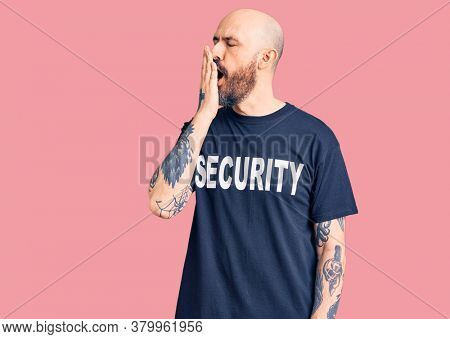 Young handsome man wearing security t shirt bored yawning tired covering mouth with hand. restless and sleepiness.