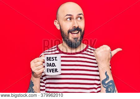 Young handsome man drinking mug of coffe with best dad ever message pointing thumb up to the side smiling happy with open mouth