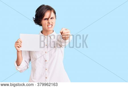 Beautiful young woman with short hair holding blank empty banner annoyed and frustrated shouting with anger, yelling crazy with anger and hand raised
