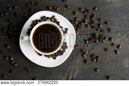 Coffee Cup With Roasted Coffee Beans On Wooden Table Background. Mug Of Black Coffe With Scattered C