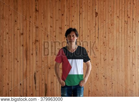 Man Wearing Palestine Flag Color Shirt And Standing With Two Hands In Pant Pockets On The Wooden Wal
