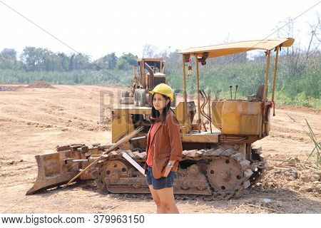 Female Civil Engineer Or Architect With Yellow Helmet Standing And Turn Sideways With Bulldozer Truc