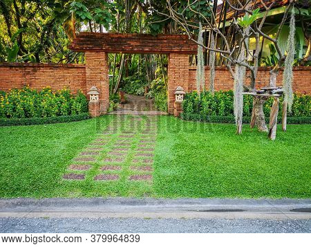 Natural Orange Clay Brick Arched Wall Entrance In A Tropical Garden With Pattern Of Brown Laterite W