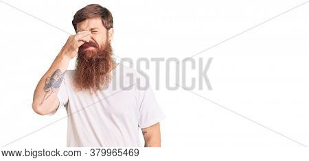 Handsome young red head man with long beard wearing casual white tshirt smelling something stinky and disgusting, intolerable smell, holding breath with fingers on nose. bad smell