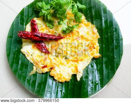 Omelette With Coriander Leaves And Red Chillies In A Banana Leaf.the Banana Leaf Has Green Color And