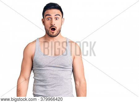 Young handsome man wearing swimwear and sleeveless t-shirt afraid and shocked with surprise and amazed expression, fear and excited face.