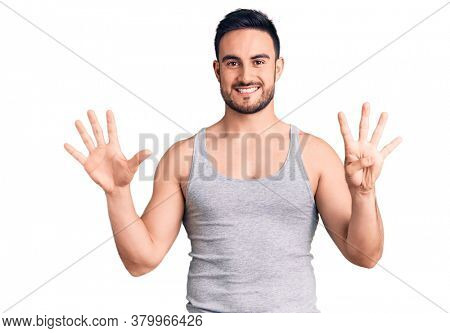 Young handsome man wearing swimwear and sleeveless t-shirt showing and pointing up with fingers number nine while smiling confident and happy.