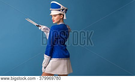 Beautiful Young Woman From The Orchestra. A Drummer In A Blue Uniform With Drumsticks, Copy Space