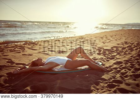 Attractive blonde surf girl posing on the beach with surfboard