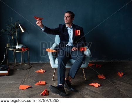 Young Man And Orange Paper Planes. Goal Planning, Concept Of Ambition And Goal Setting