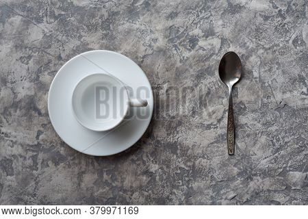 Top View Of Empty Cup On Saucer And Spoon On Gray Background