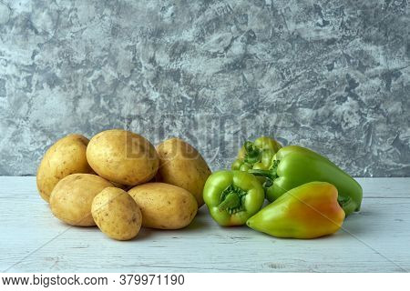Fresh Raw Potatoes And Green Pepper On Textured Background