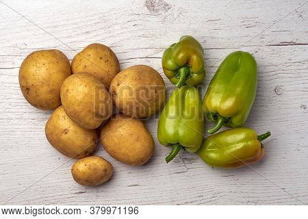 Top View Of Fresh Raw Potatoes And Green Peppers On Wooden Background