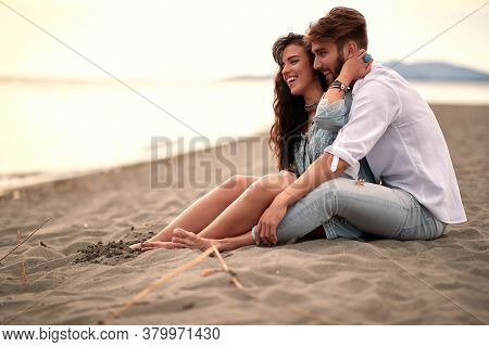 young beautiful couple sitting on the sandy beach, enjoying, smiling, hugging. love, leisure, relax, tenderness concept