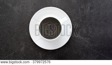 Top Down View Of Empty Coffee Cup On White Saucer Placed On Dark Stone Table