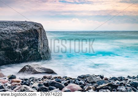 Sunrise Over The Sea. Stone On The Foreground. Colorful Rounded Stones On Beach