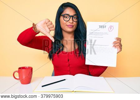 Beautiful latin young woman with long hair showing a failed exam with angry face, negative sign showing dislike with thumbs down, rejection concept
