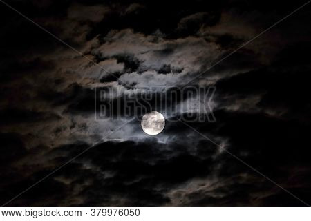 Mystical Landscape With White Full Moon In The Night Sky Obscured By Cumulus Clouds