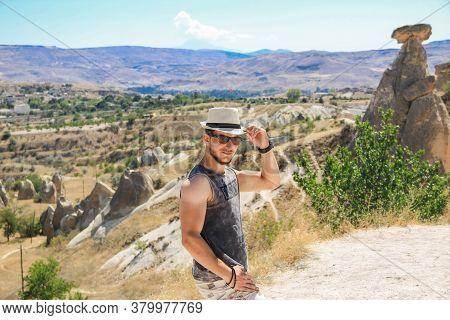 Cappadocia, Turkey 11 March 2019:\na Young Man Stands Amidst Huge Rocks.