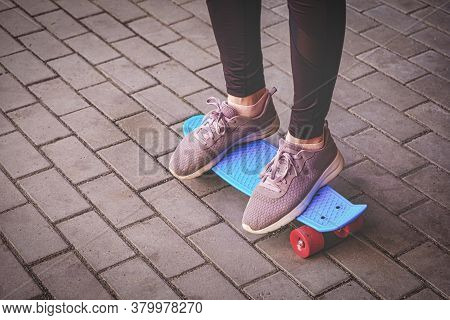 Teenage Girl In Spurt Shoes Is Standing On Small Pennyboard Skateboard On Footpath