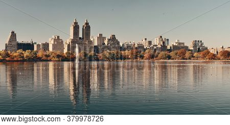 Skyline panorama with apartment skyscrapers over lake with fountain in Central Park in midtown Manhattan in New York City