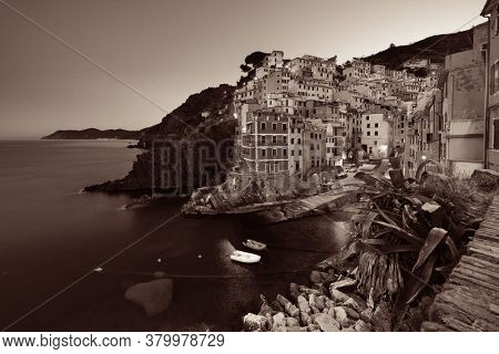 Riomaggiore waterfront black and white view with buildings in Cinque Terre at night, Italy.