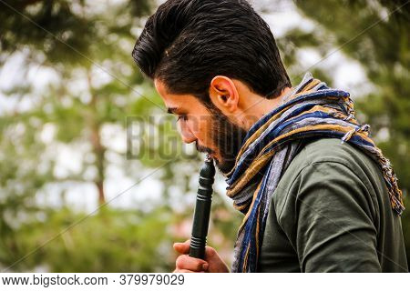 Istanbul, Turkey April 10, 2019:\na Handsome Bearded Man Drinking Hookah In The Open Air