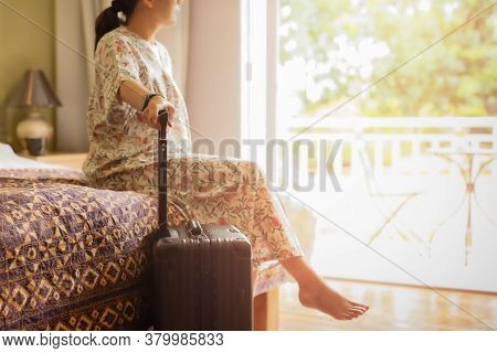 Woman Traveler With Luggage Sitting On The Bed In Hotel Room With Garden View.